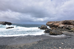 Waves Crashing on the Shore of the Black Sand Stone Beach Stock Images