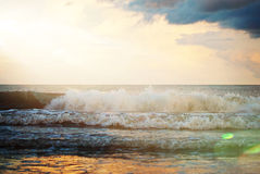 Waves crashing on shore with a gorgeous sunflare hitting the water. Stock Photos