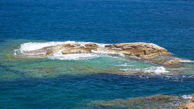 Waves crashing on small rocks over the quiet Mediterranean Sea Stock Image