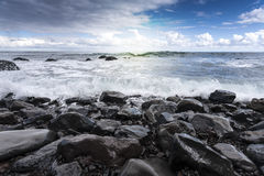 Waves Crashing Stones on Beach. With Blue Sky stock image