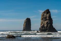 Waves crashing on vertical rocks protruding in Cannon Beach, Oregon, USA. stock photos