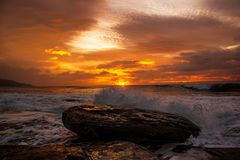 Waves crushing a rock during sunrise. Sea sunrise at the great Ocean Road, Victoria, Australia. Waves crushing a rock during sunrise. Sea sunrise at the great stock photo