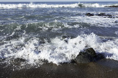 Waves crushing on a rocky beach making sea foam on Moonstone Beach Royalty Free Stock Photography