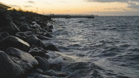 Waves crushing and splashing into a rocky shore. Ocean waves crushing and splashing into a rocky shore at sunet. A dock and boat mast in the background stock footage