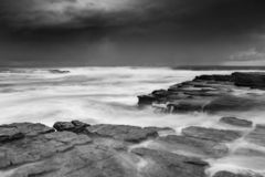 Waves engulf the rock shelf as moody weather increases swells stock photography