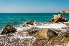Waves entering Pissouri pebble beach through large rocks in the water, Cyprus. Waves entering Pissouri pebble beach through large rocks in the water, Limassol Royalty Free Stock Image