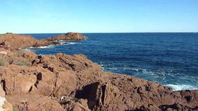 Waves and Esterel massif, France. Waves of the Mediterranean sea on big red rocks of Esterel massif in south of France by beautiful weather stock video