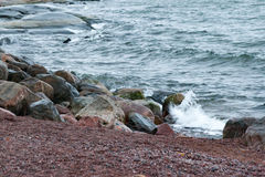 The waves fighting about coastal stones on the seashore in rainy weather Stock Photography