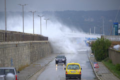 Waves flooding breakwater and cars Stock Image