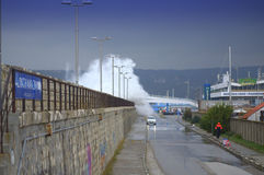 Waves flooding breakwater and cars Royalty Free Stock Photo