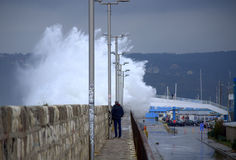 Waves flooding breakwater thrill seekers Stock Image