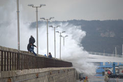 Waves flooding breakwater thrill seekers. Huge waves flooded Varna breakwater walking people and cars on the street to marine station, the port is closed. Orange Royalty Free Stock Photography