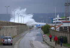 Waves flooding breakwater thrill seekers. Huge waves flooded Varna breakwater walking people and cars on the street to marine station, the port is closed. Orange Royalty Free Stock Photo