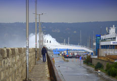 Waves flooding breakwater thrill seekers. Huge waves flooded Varna breakwater walking people and cars on the street to marine station, the port is closed. Orange Stock Images