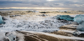 Waves flowing off a beach. Stormy ocean at the Southern Iceland washes over volcanin beach Royalty Free Stock Image