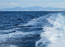 The waves and foam from a boat in a bright summer day. Islands and mountains in the background. Summer vacation royalty free stock photography