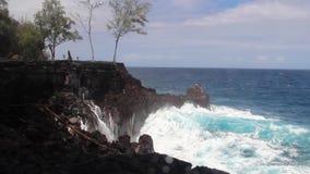 Waves and foam crashing over rocks 30 metres up high, in Big Island, Hawaii