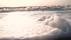 Waves, with foam, reach camera and come back against background of sea, the surf, the blue sky stock video