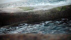 Waves and foam on rocky beach. Breakwater in ocean stock video