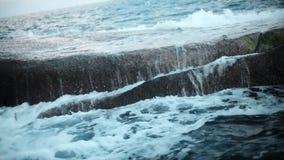 Waves and foam on rocky beach. Breakwater in ocean stock video footage