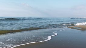 Waves with foam on the sea green color, long sandy beach stock footage