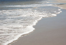 Waves and foam on shore. Waves wash onto a sandy beach Royalty Free Stock Photos