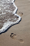 Waves and footprints on beach Royalty Free Stock Photos