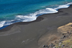 Waves form a circular patter. As it crashes on the black sand beach of Fonti di Billa Stock Images