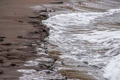 Waves forming drawings in the sand. Waves forming beautiful drawings in the sand Royalty Free Stock Photo