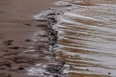 Waves forming drawings in the sand. Waves forming nice drawings in the sand Stock Photo