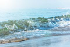 Waves with a green tint on the beach stock images