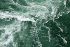 Waves in green water. With white ripples Stock Photo