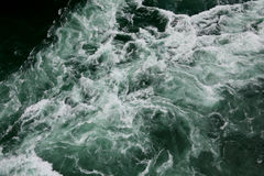 Waves in green water. With white ripples Royalty Free Stock Images