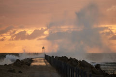 Waves hit the pier in front of the sunset at Nr. Vorupoer at the North Sea Coast in Denmark Royalty Free Stock Image