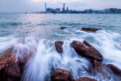 Waves hit rock in Victoria Harbour of Hong Kong Stock Photo