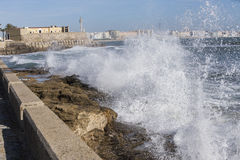 Waves hit the rocks on the promenade of the La Caleta beach in C Royalty Free Stock Photo