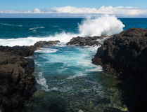 Waves hit rocks at Queens Bath Kauai Stock Images