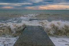 Waves hit the stone sea pier. Splashes scatter in all directions royalty free stock photo