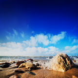 Waves hiting rocks on the sunny beach. Waves hiting rocks on the beautiful natural beach. Blue sunny sky Royalty Free Stock Images