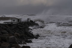 Waves hitting against the pier during storm at the North Sea coast in Denmark Stock Images