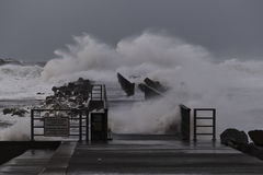 waves hitting against the pier during the storm in Nr. Vorupoer on the North Sea coast Stock Photos