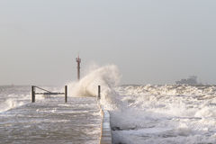 Waves hitting the pier. As waves are hitting the pier in a storm, a ship is approaching the safe harbor Royalty Free Stock Images