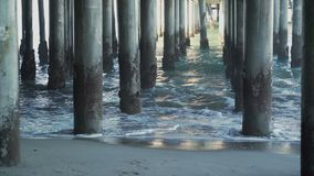 Waves hitting the pilings under the Santa Monica Pier. The Santa Monica Pier is a large double-jointed pier located at the foot of Colorado Avenue in Santa stock video