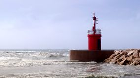 Waves hitting a red lighthouse tower of a harbor entrance. stock footage