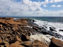 Waves hitting the reddish cliffs in the wind a sunny day on the Westcoast of Sweden, Halmstad. A cloudy, windy but still sunny August day the ocean waves threw stock images