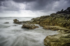 Waves hitting the rock at the seashore. soft look wave and dramatic dark cloud Stock Photos