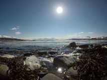 Waves hitting rocky seashore with bright sun and snowy mountain Stock Images
