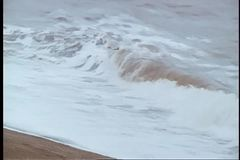 Waves hitting shoreline on overcast day stock video footage