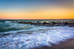 Waves and a jetty at sunset in the Atlantic Ocean at Edisto Beac Stock Image