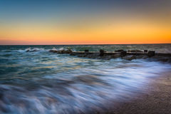 Waves and a jetty at sunset in the Atlantic Ocean at Edisto Beac Royalty Free Stock Photo